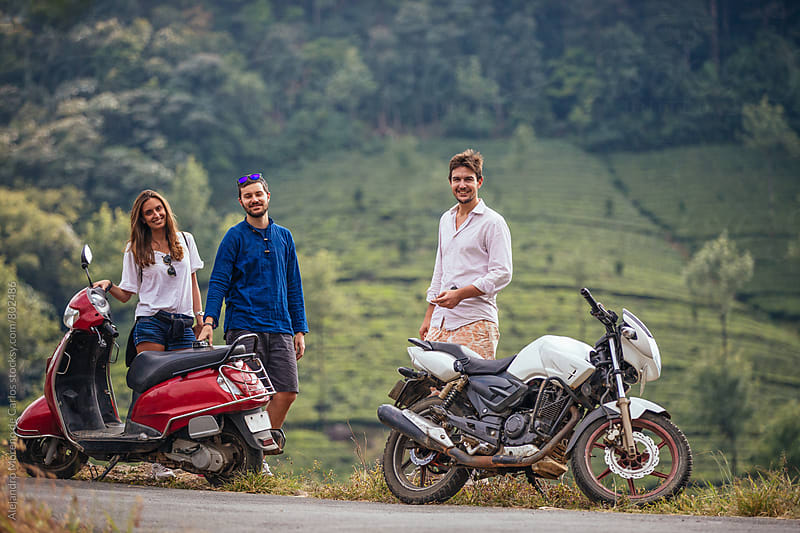 Three young friends standing next to motorbikes in front of a hill of tea plantations by Alejandro Moreno de Carlos for Stocksy United