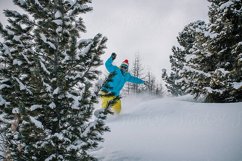 Young man snowboarding in powder snow by Davide Illini for Stocksy United