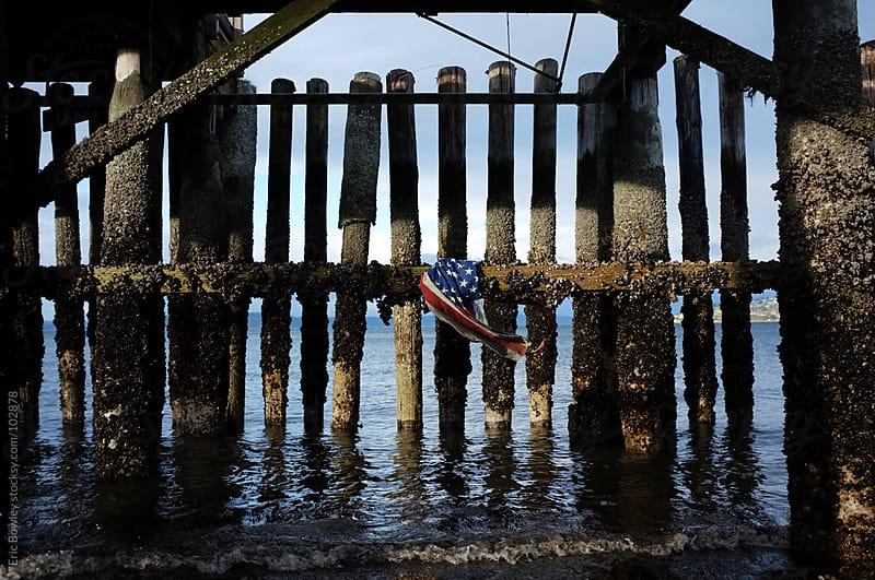American Flag Underneath Peir  by Eric Bowley for Stocksy United