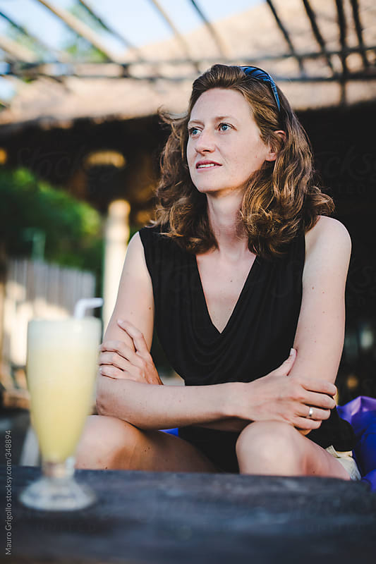 Woman drinking a juice in a Balinese bar by Mauro Grigollo for Stocksy United