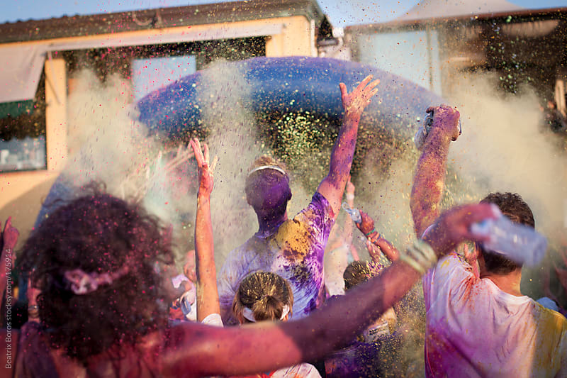 During outdoors concert crowd is throwing holi powder in the air by Beatrix Boros for Stocksy United