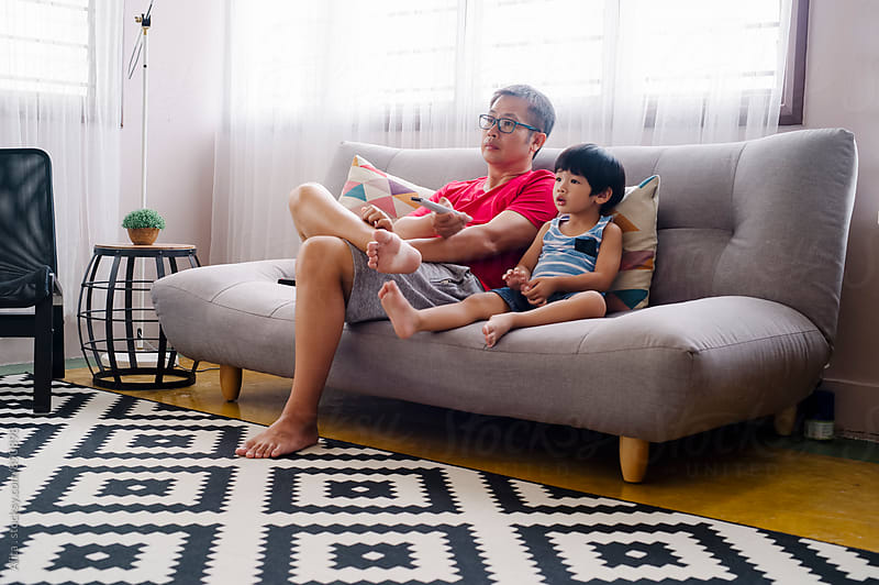 Father and son watching TV together by Alita Ong for Stocksy United