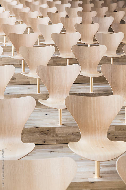 Aligned designer wooden chairs in a lecture hall by Lior + Lone for Stocksy United