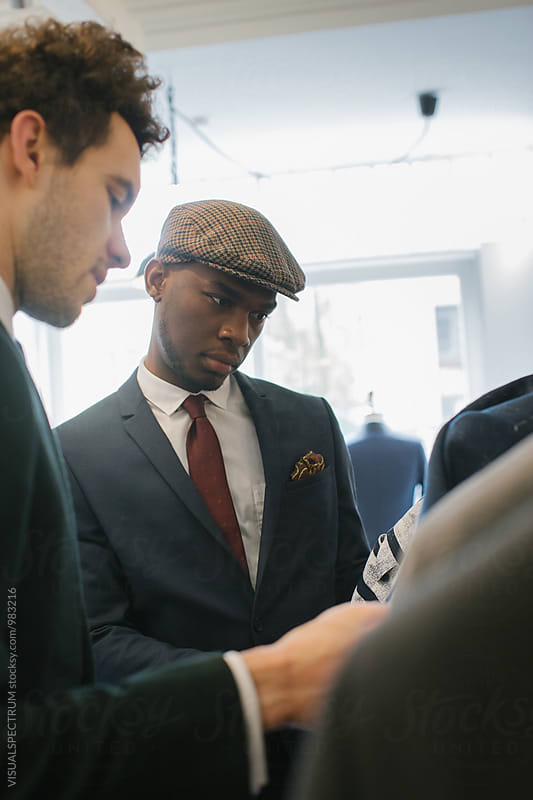 Men's Fashion Shopping - Young Caucasian Shop Assistant Showing Suits to Young Black Customer by VISUALSPECTRUM for Stocksy United