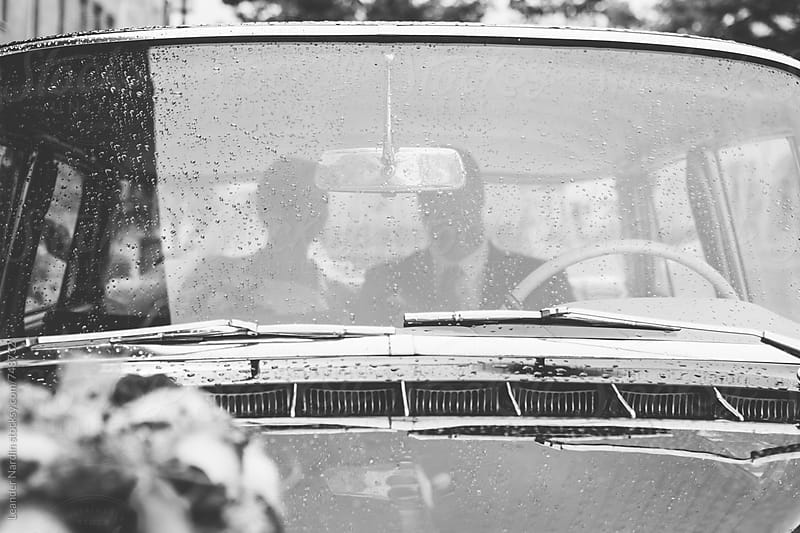 bridal couple sitting in an oldtimer with wedding flowers on the hood in black and white by Leander Nardin for Stocksy United