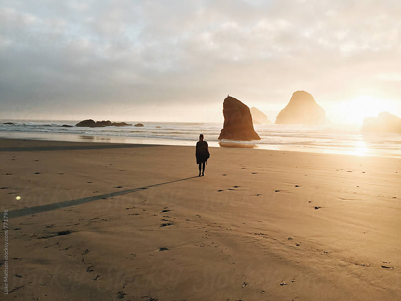 Young Woman Standing On Coastal Beach Casting Long Shadow At Sunset by Luke Mattson for Stocksy United