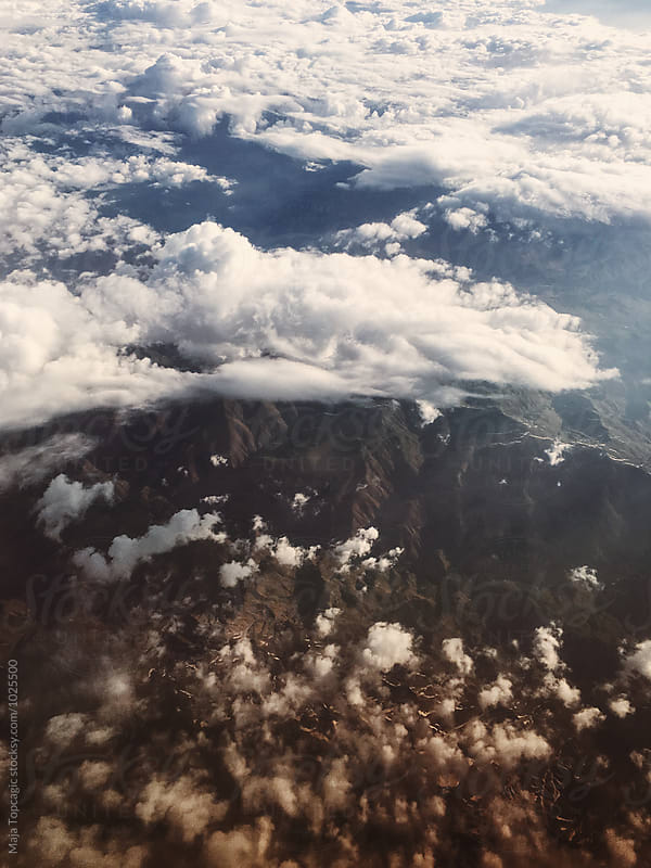 Aeroplane shot of a mountain beneath the clouds by Maja Topcagic for Stocksy United