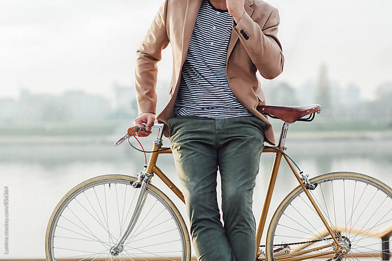 Businessman on a Bicycle by the River by Lumina for Stocksy United