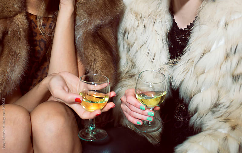 friends in fur drinking by Sonja Lekovic for Stocksy United