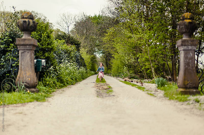 Little girl running towards the exit on an long entrance way by Cindy Prins for Stocksy United