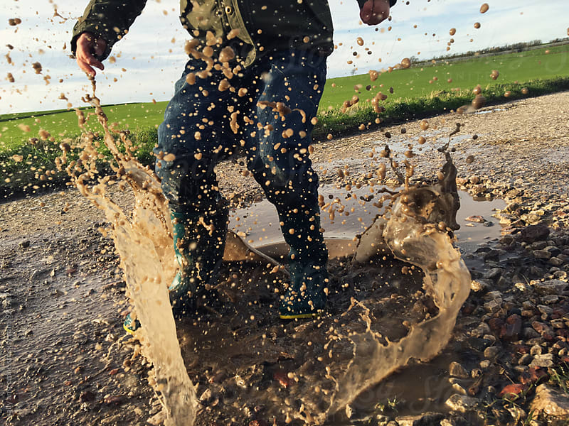 Child jumping in a muddy puddle by sally anscombe for Stocksy United