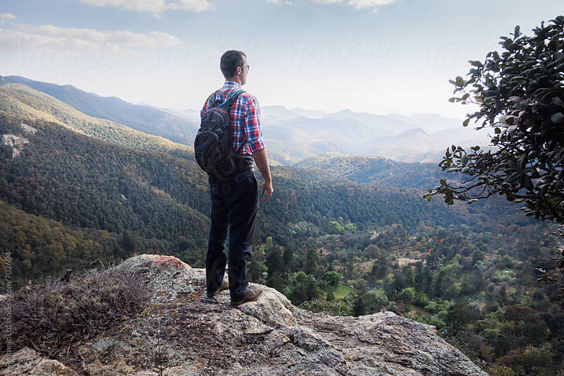 Man looking out over beautiful valley from mountain peak by Per Swantesson for Stocksy United