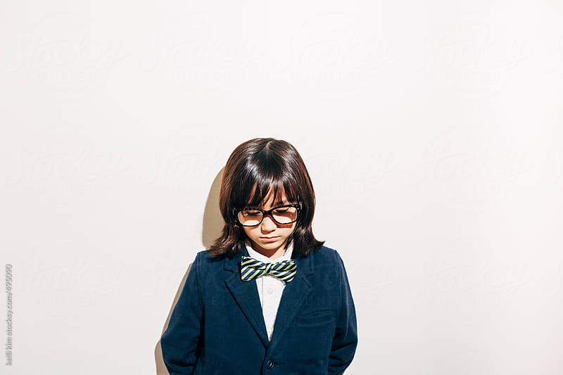 Young boy in glasses and bow tie stands alone, appearing sad by kelli kim for Stocksy United