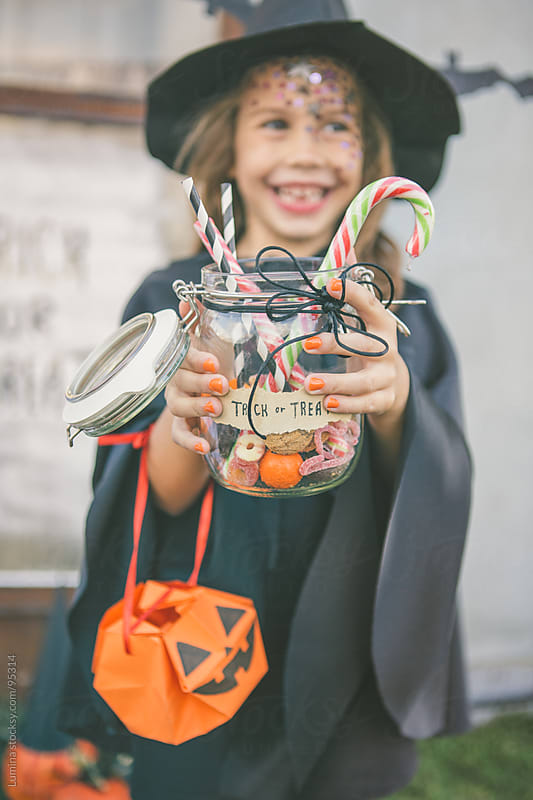 Smiling Witch With Halloween Treats by Lumina for Stocksy United