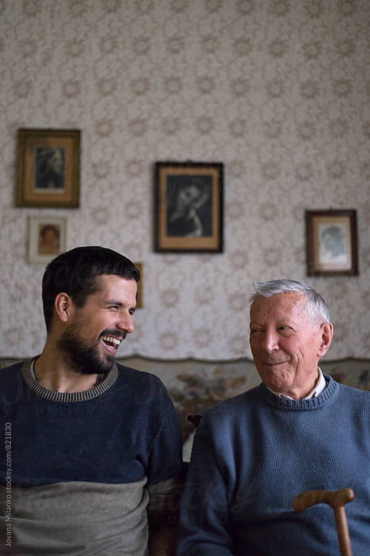 Adult grandson hugging his grandfather  by Jovana Milanko for Stocksy United
