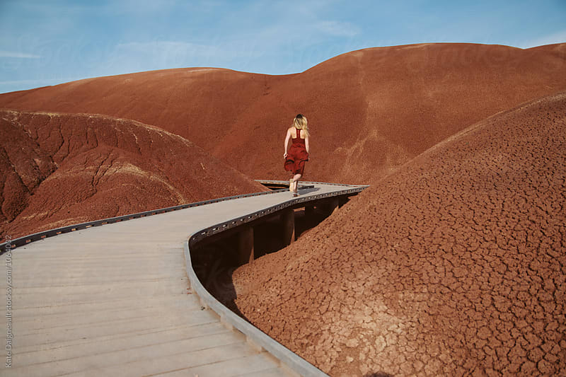 Young woman in red dress running through red painted hills. by Kate Daigneault for Stocksy United