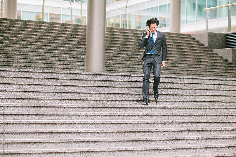 Young Asian businessman running down the stairs while calling on the phone by Ivo de Bruijn for Stocksy United
