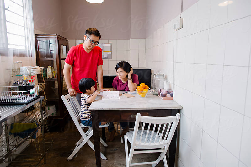 Asian family having conversation in a kitchen by Alita Ong for Stocksy United
