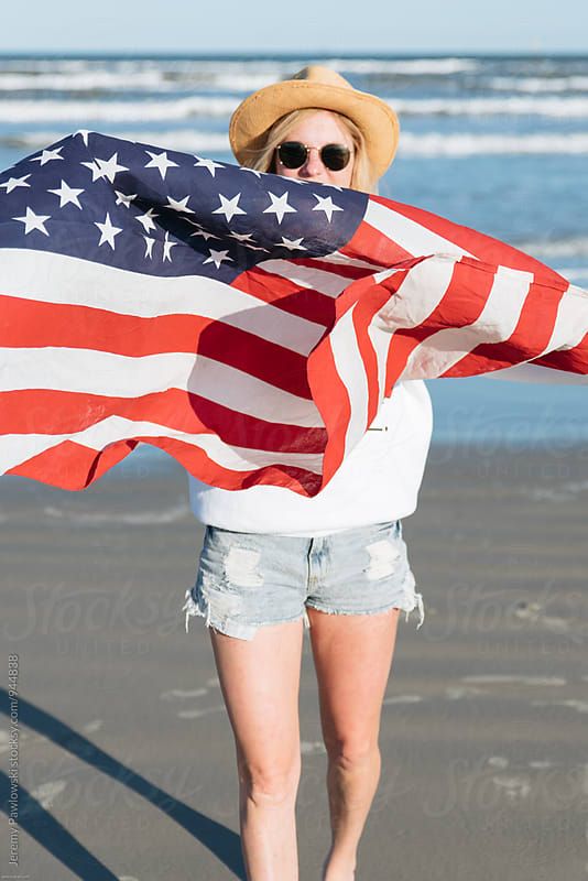 Girl in sunglasses holding American Flag. 4th of July at the ocean. by Jeremy Pawlowski for Stocksy United