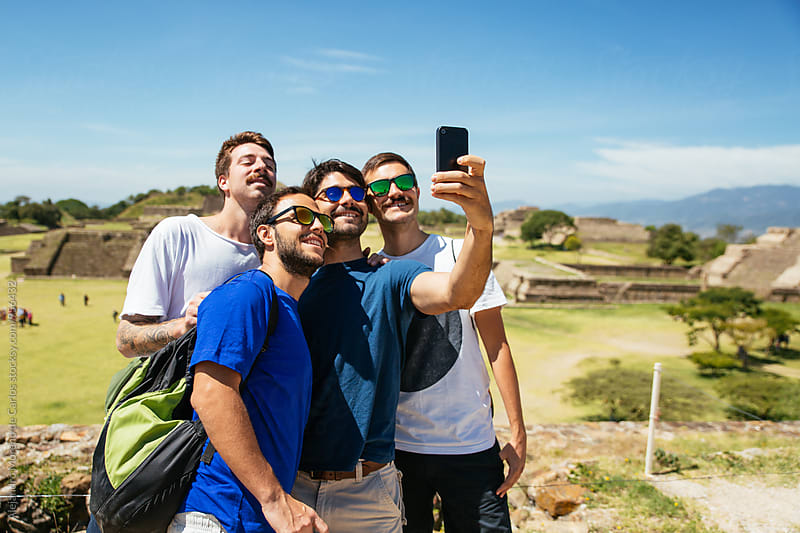 Four friends taking selfie together in touristic landmark by Alejandro Moreno de Carlos for Stocksy United