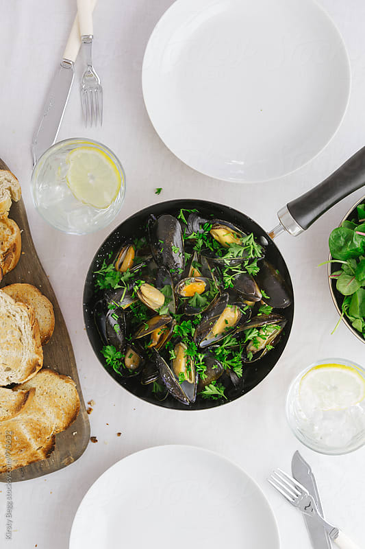Pan of mussels in garlic butter sauce on dinner table by Kirsty Begg for Stocksy United