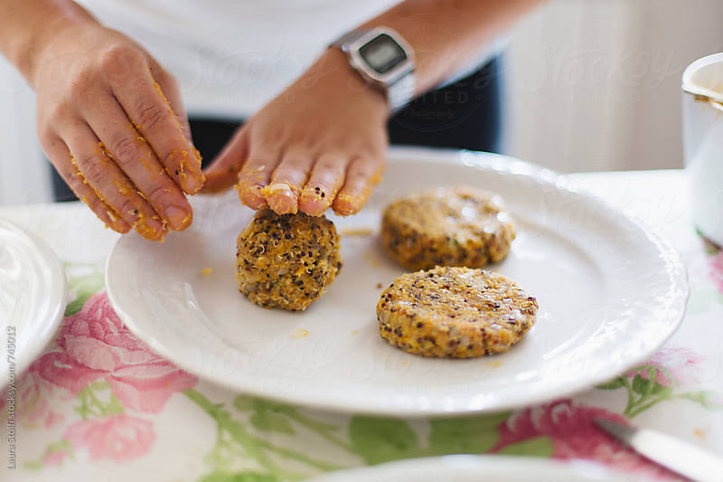 Vegan burgers in the making; close up of woman's hand shaping quinoa and sweet potatoes mix by Laura Stolfi for Stocksy United