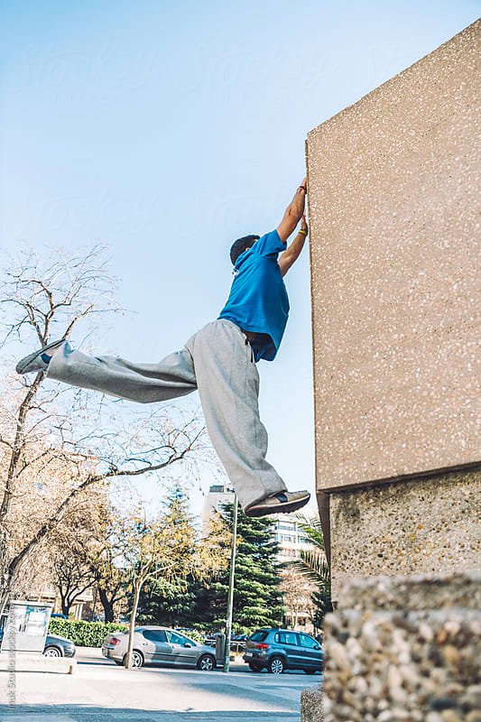 Man jumping and clutching during a parkour training in a city by Inuk Studio for Stocksy United