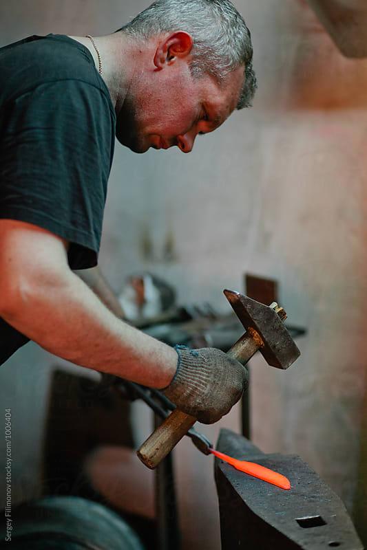 blacksmith makes a knife by Sergey Filimonov for Stocksy United