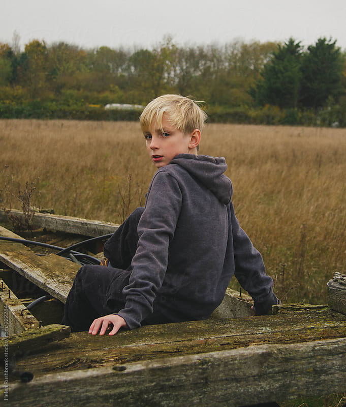 A boy sitting on an old farm trailer by Helen Rushbrook for Stocksy United
