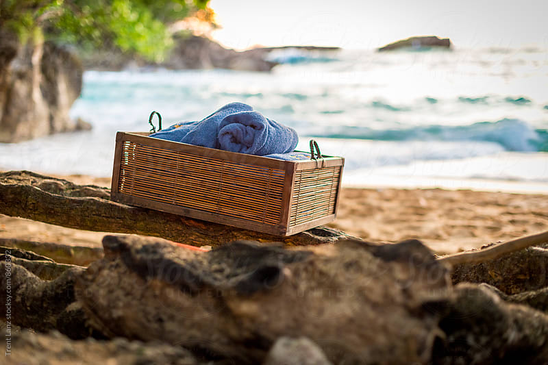 Beach towels in box on serene shoreline by Trent Lanz for Stocksy United