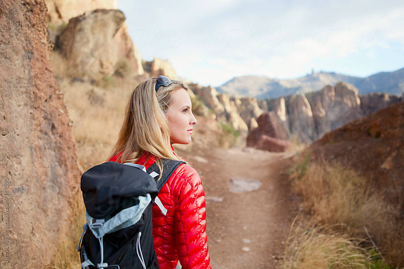 Beautiful female hiker pauses on trail by Linzy Slusher for Stocksy United