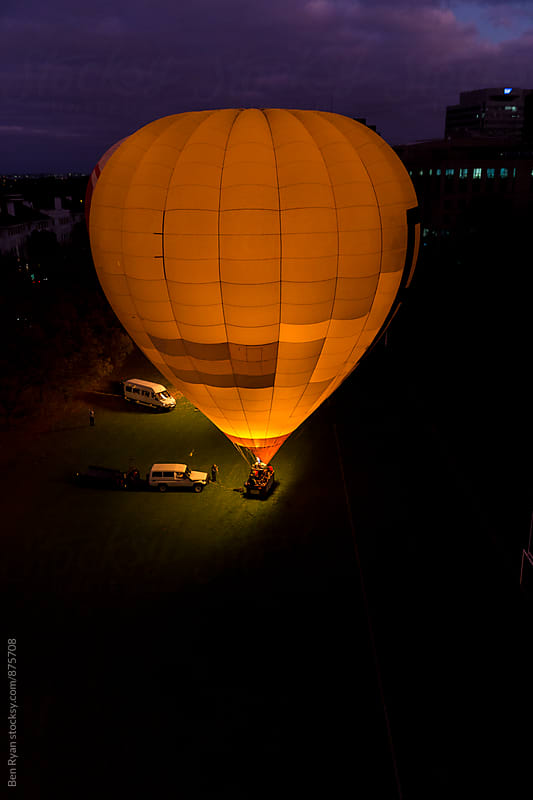 Yellow hot air balloon preparing to launchand support vehicles from elevated position by Ben Ryan for Stocksy United