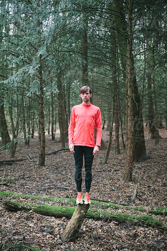 A young runner standing on a tree trunk in the forest by Ivo de Bruijn for Stocksy United