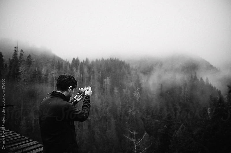 guy taking photos in forest by Dylan M Howell Photography for Stocksy United