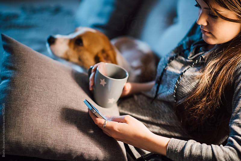 Woman using a mobile phone and cuddling a dog by Boris Jovanovic for Stocksy United