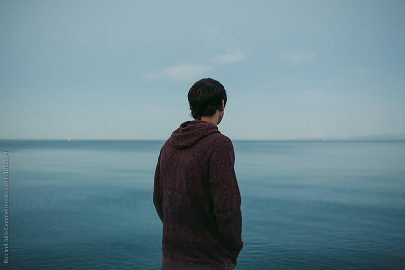 Portrait of young caucasian boy standing near water on beach by Rob and Julia Campbell for Stocksy United