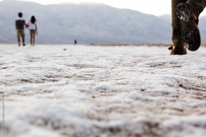 Tourists walk out on Salt Flats in the hot desert. by Holly Clark for Stocksy United