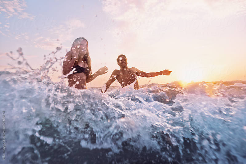 Sexy Couple swimming in the sea at Sunrise by Aila Images for Stocksy United
