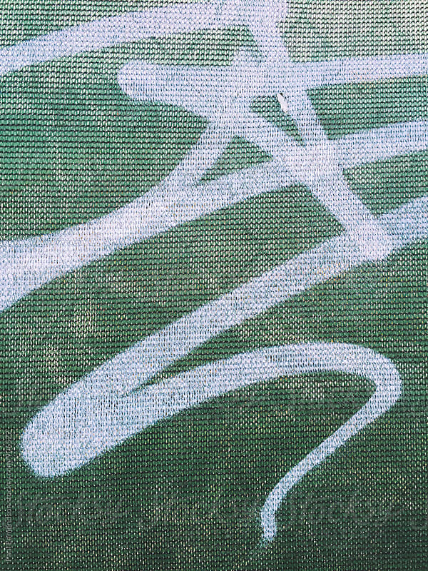 Graffiti tag on green fabric covering fence by Paul Edmondson for Stocksy United