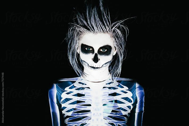 Spooky portrait of woman in skeleton costume and halloween make up on black background by Aleksandar Novoselski for Stocksy United