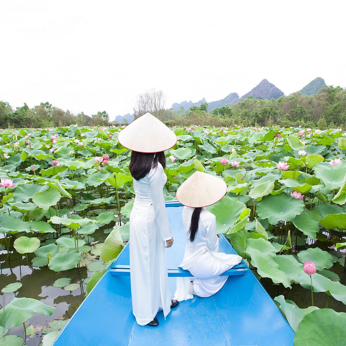Two Vietnamese Women On Boat In Lake With Lotus Flowers Stocksy