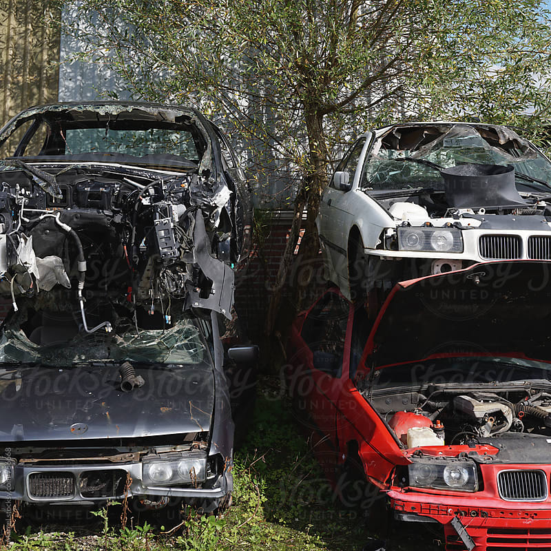 Wrecked cars stacked on top of eachother at a scrapyard by Marcel for Stocksy United