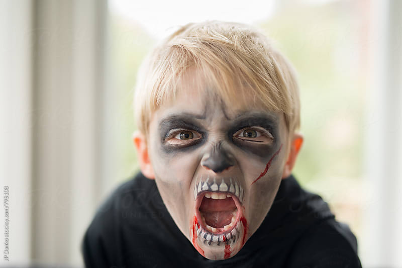 Little Boy With Scary Zombie Ghoul Halloween Costume Make Up Making Scary Face by JP Danko for Stocksy United