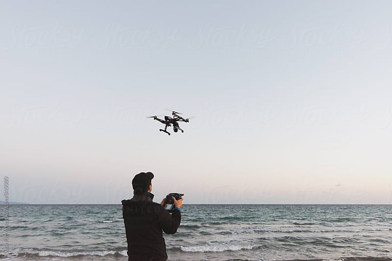 Man using a drone on the beach by Luca Pierro for Stocksy United