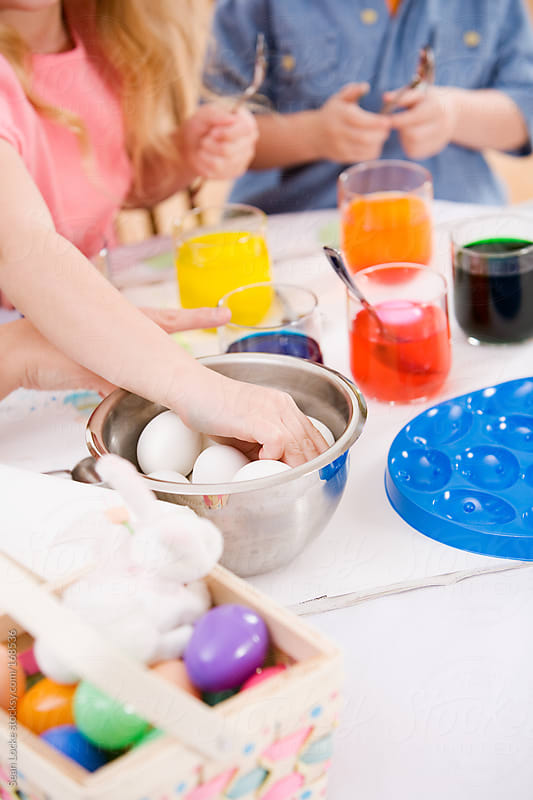 Easter: Girl Reaches For Egg To Color by Sean Locke for Stocksy United