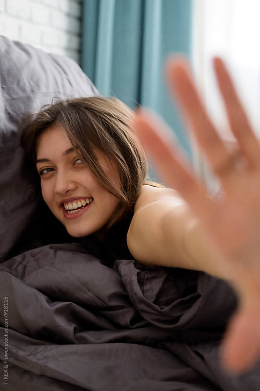Smiling brunette looking at camera while lying on bed by T-REX & Flower for Stocksy United