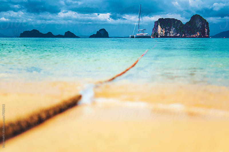 Thai beach with parked yacht in the distance by Wizemark for Stocksy United