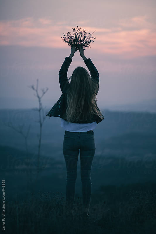 woman offering plants to the sunset by Javier Pardina for Stocksy United
