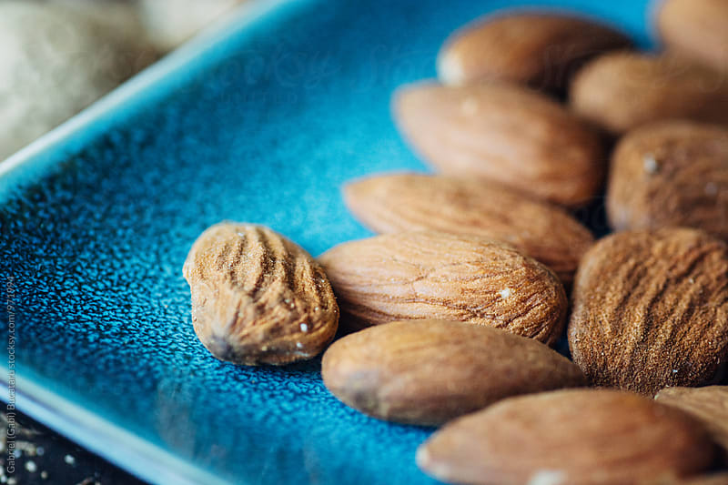 Closeup of almond kernels on a blue plate by Gabriel (Gabi) Bucataru for Stocksy United