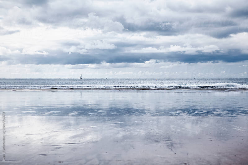 Beach at low tide on a cloudy day by Ivan Bastien for Stocksy United
